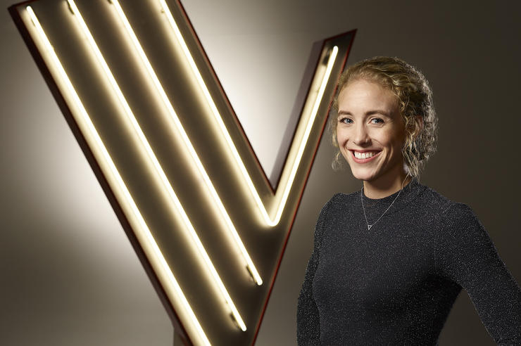 University of Iowa alumna Cali Wilson standing before a logo for The Voice