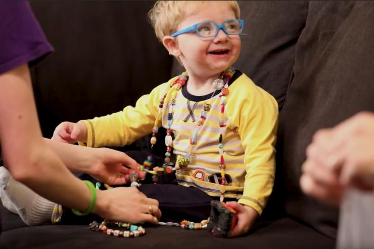 a young boy who received bone marrow transplant at the UI Stead Family Children's Hospital is shown wearing a necklace that symbolizes all the procedures he's had to endure