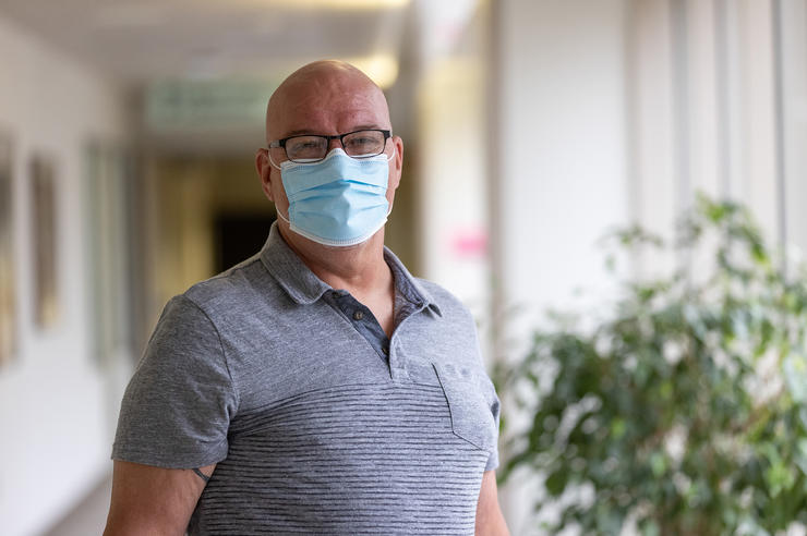 a man wearing a face mask standing indoors