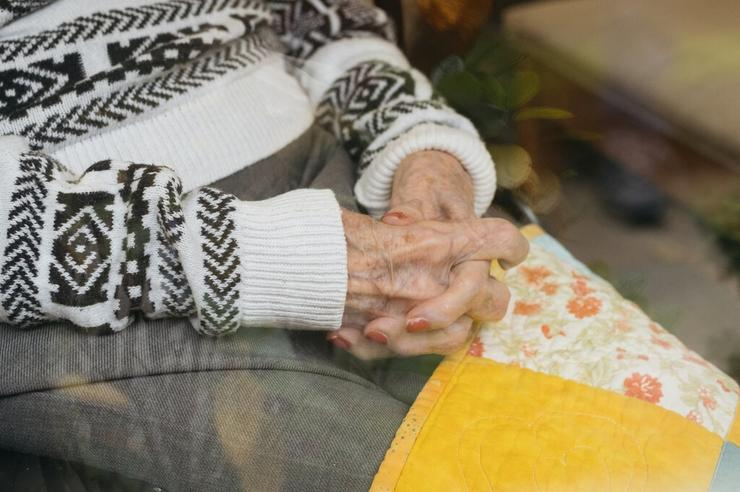 clasped hands in lap