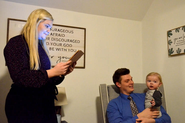 Halle Howard uses a tablet while Ethan Howard holds their son Charlie in their Springville home