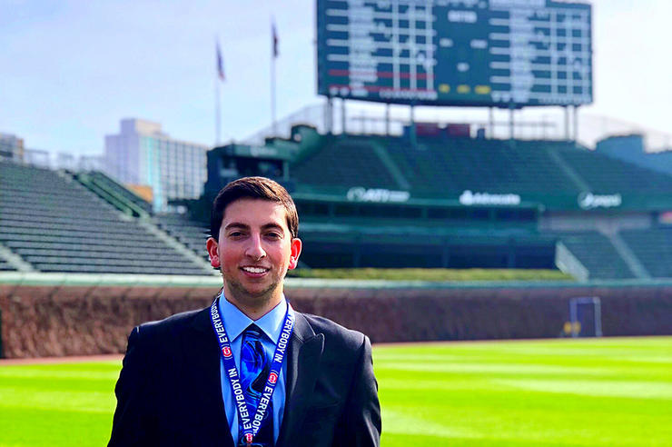University of Iowa alumnus Jared Mandel standing at Wrigley Field with the iconic scoreboard in the background