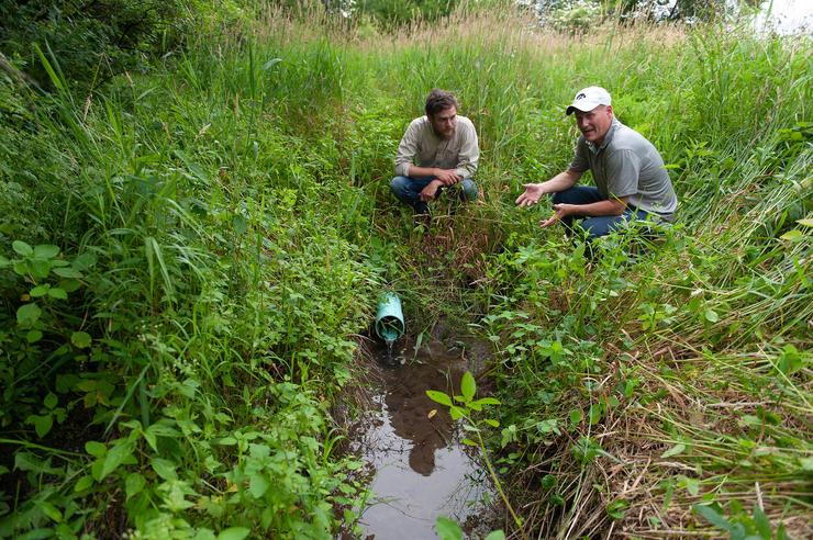 two men speaking in field