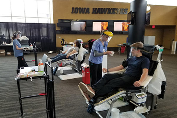 health care professionals and participants at a blood drive held at the university of iowa's carver-hawkeye arena