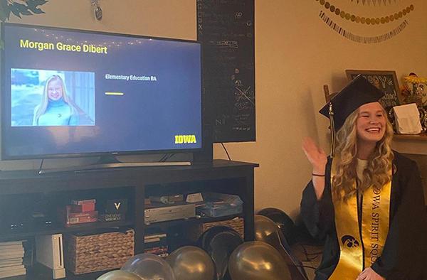 University of Iowa graduate Morgan Dibert smiles and waves in her home during virtual commencement ceremonies