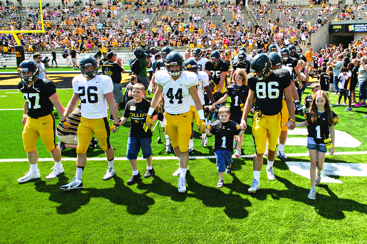 university of iowa football players and kid captains take the field in swarm formation