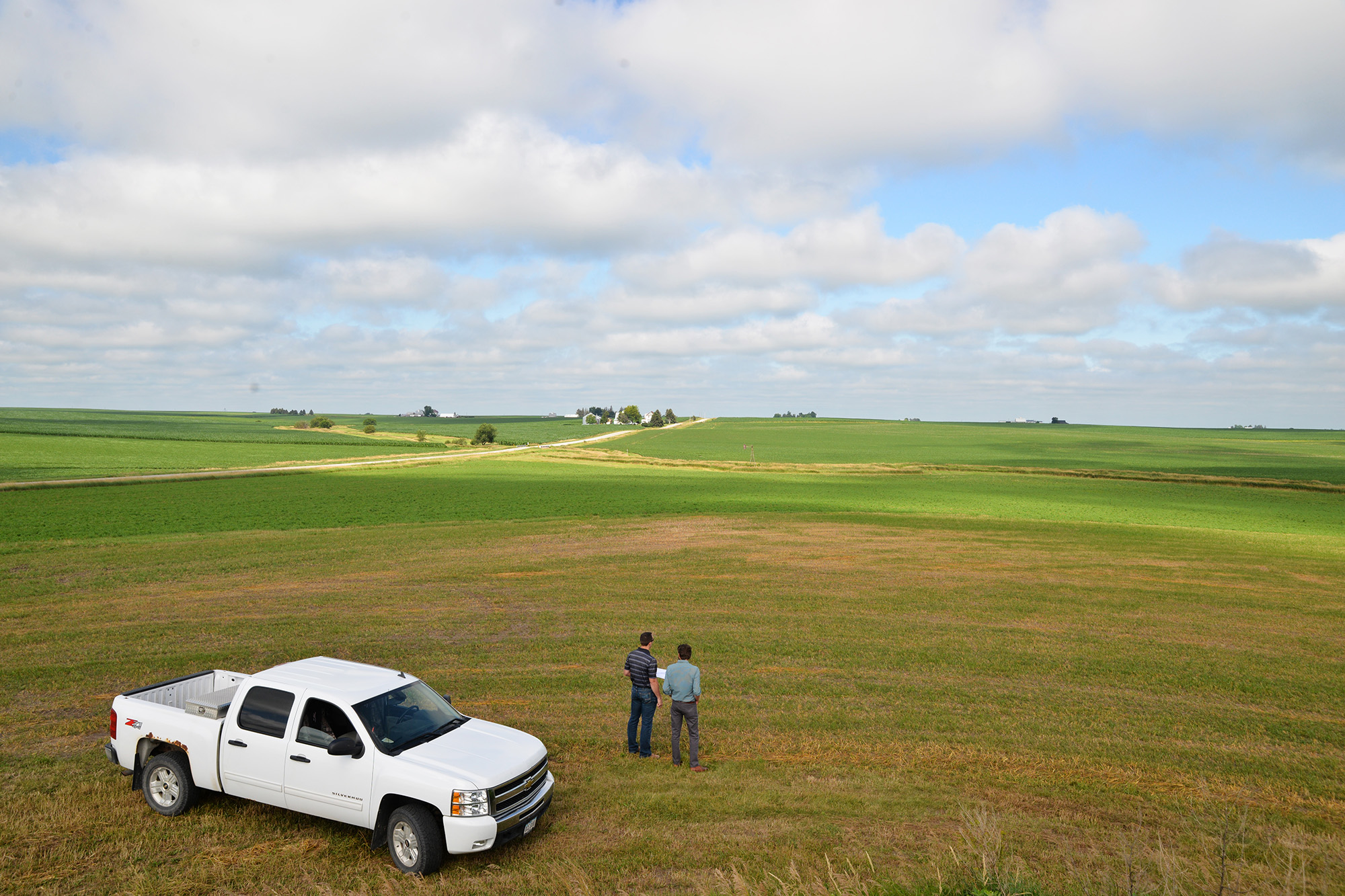 two men stand in a field and discuss the watershed and landscape above the community of Vinton