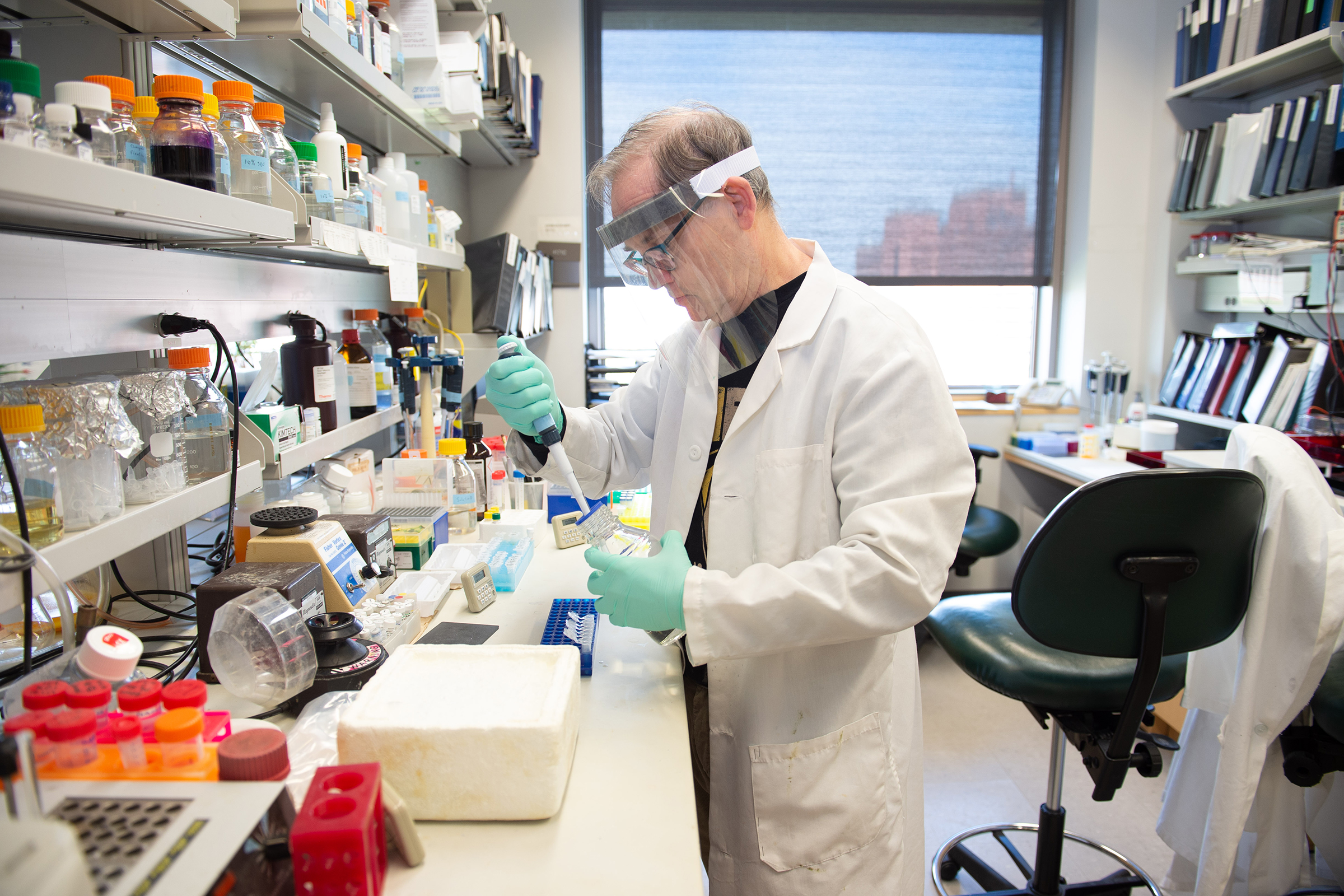 Research specialist Charles Searby prepares coronavirus RNA from saliva samples for quantitative RT-PCR (reverse transcription-polymerase chain reaction), a lab method used to detect the presence of a pathogen.