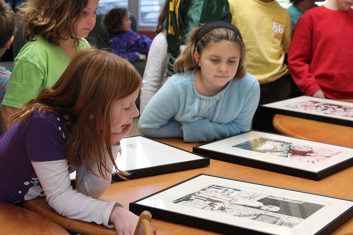 elementary school students look at artwork from the Stanley's collection